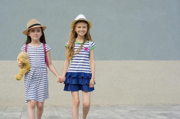 手を繋いでいる2つの小さな美しいガールフレンド