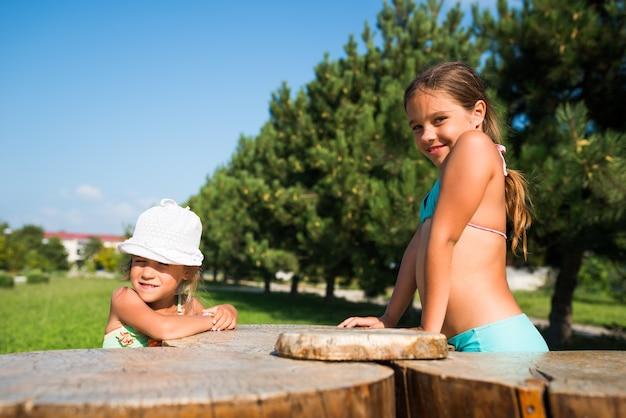 2人の小さな美しい女の子が公園で一緒に遊ぶ
