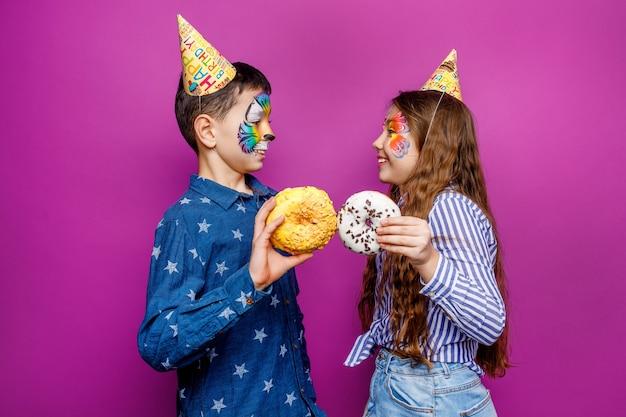 Два маленьких лучших друга держат сладкий и красочный пончик на фиолетовой стене