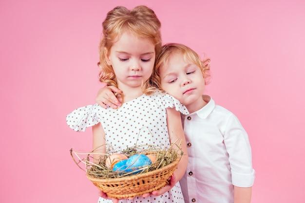 スタジオピンクの背景にひよこコックイースターを持つ2つの小さなブロンドの子供。ペットとイースター休暇を祝う美しい男の子と女の子の子供たち、籐のバスケットに塗られた卵。夢の誕生日プレゼント