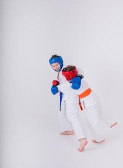 白い着物、ヘルメット、手袋をはめた2人の少年アスリートが白い壁で戦う