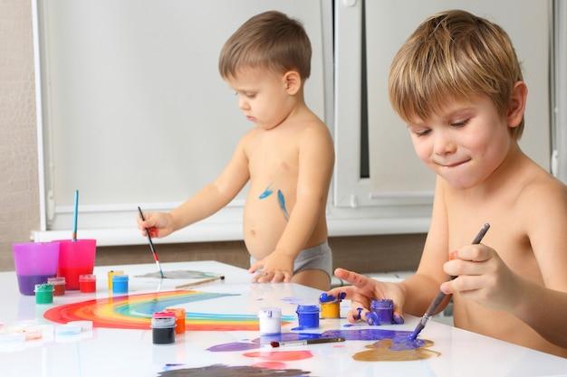 흰색 테이블에 두 개의 작은 소년 페인트