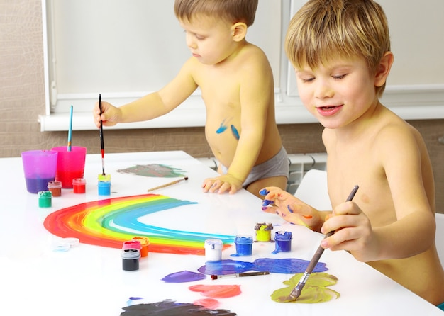 Two little boy paint on a white table. artistic creativity in children's development