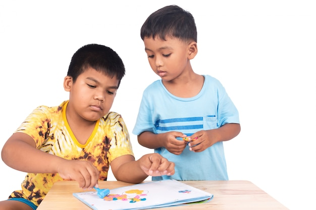Two little boy play clay on book
