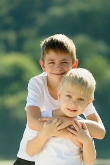 Two little boys are hugging outdoors