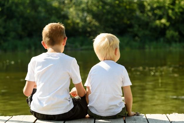 두 명의 작은 소년이 강둑의 부두에 앉아 있습니다. 우정과 형제애의 개념. 다시보기