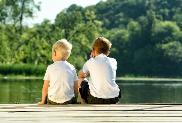 Two little boys are sitting the pier on the river bank.  of friendship and fraternity. back view