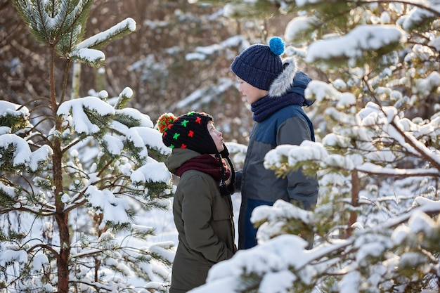 Two little boys friends hug each other in snowy winter day. brother love. concept friendship.