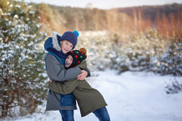 Two little boys friends hug each other in snowy winter day. brother love.