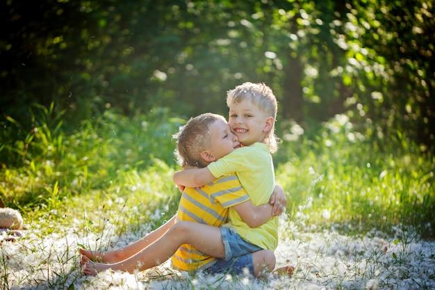 Two little boys friends hug each other in summer garden.