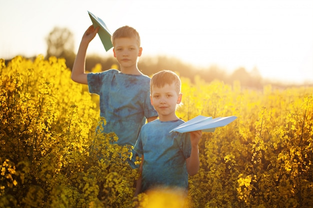 Two little boys friends with blue paper plane in summer yellow field.