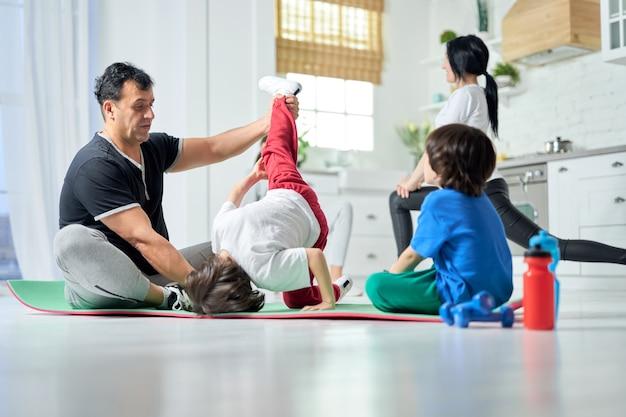 お母さんとお姉さんがバックグラウンドでエクササイズをしながら、お父さんと一緒にマットの上でヨガを練習しながら楽しんでいる2人の男の子。自宅で朝のトレーニングをしているアクティブなヒスパニック家族