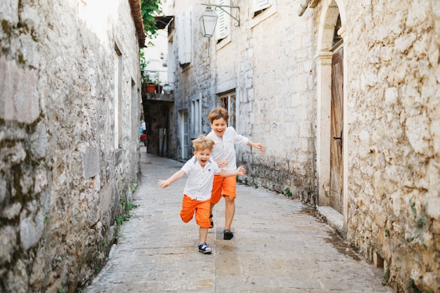 주황색 반바지와 흰색 티셔츠를 입은 두 소년이 페라스트 몬테네그로의 거리를 달리고 있습니다.