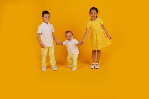 Два маленьких мальчика в желтых брюках и белой футболке держат за руку сестру в желтом платье.
