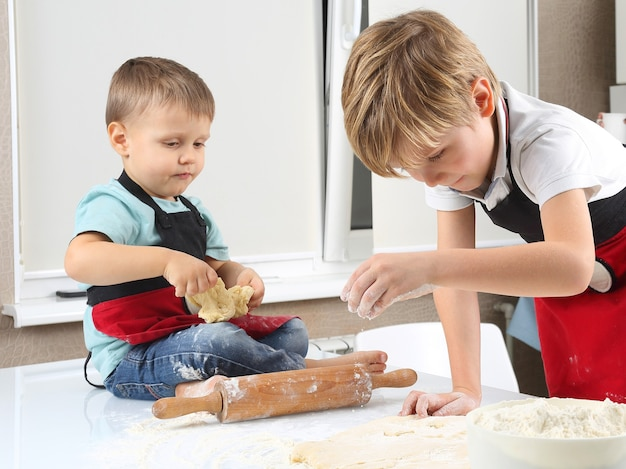 Two little boys knead the dough on the kitchen table