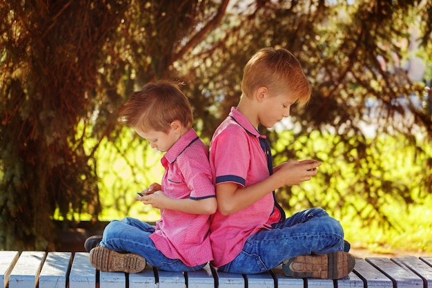 Two little boys playing games on mobile phone in sunny day, sitt