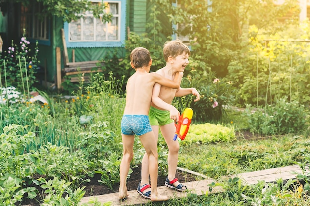 Two little boys playing with water guns on hot summer day cute children having fun with water on the