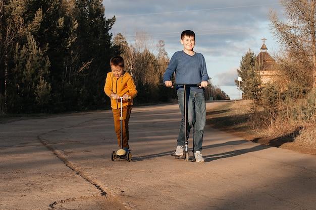 2人の男の子がスクーターに乗っています。暖かい夏または春の日。兄弟は一緒に楽しんでいます。友情の概念。