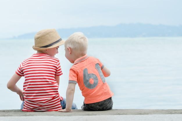두 명의 작은 소년이 바다와 산을 배경으로 부두에 앉아 있습니다. 다시보기