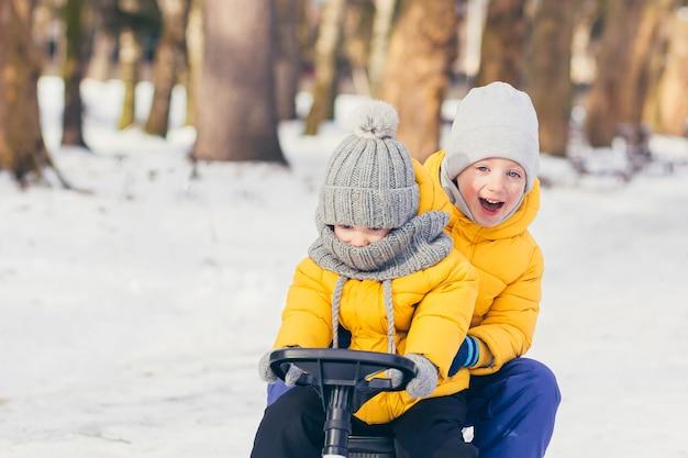 Два маленьких мальчика гуляют вместе в зимнем парке и веселятся
