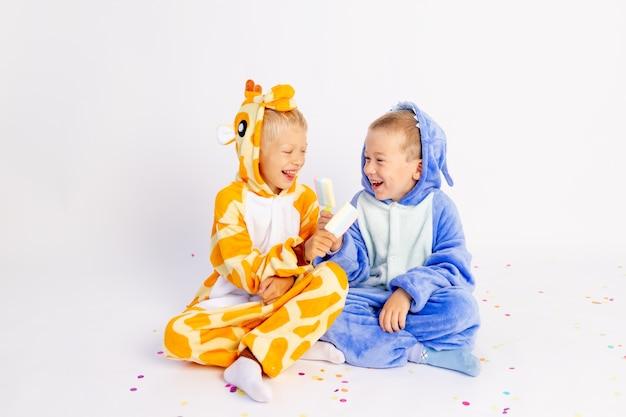 Два младших брата в ярких костюмах на белом изолированном фоне едят мороженое и балуются
