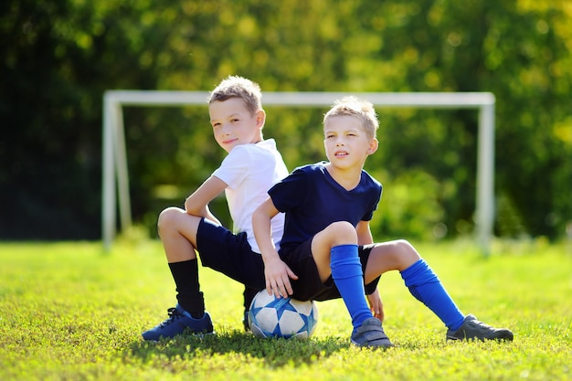 Two little brothers having fun playing a soccer game on sunny summer day