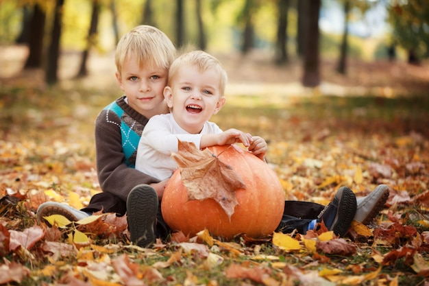 Two little brothers sitting on grass and embracing with huge pumpkin in autumn day
