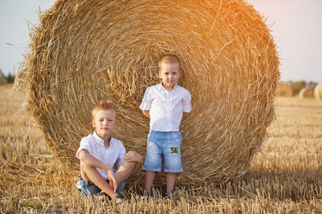 Two little brothers sitting near a haystack in wheat field on warm and sunny summer day