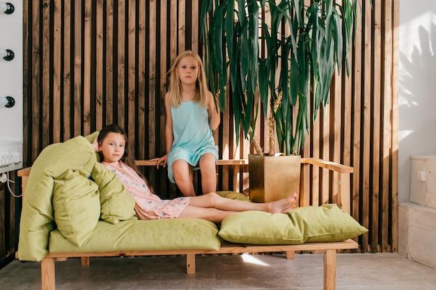 スタイリッシュなドレスでベッドでリラックスした2つの小さな不注意な女の子