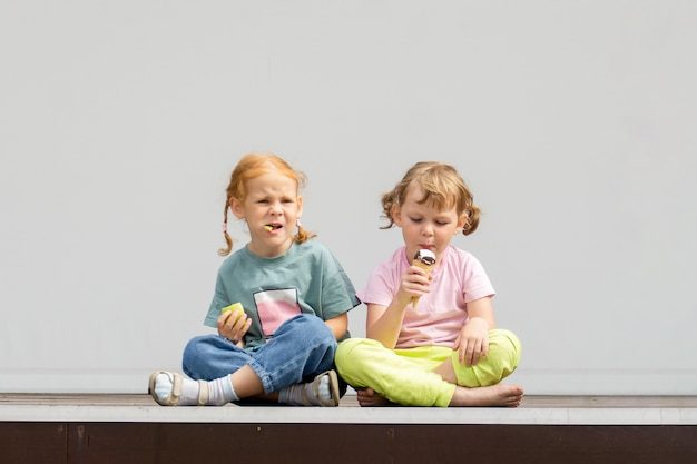Two little caucasian cute girls are sitting cross-legged and eating ice cream.