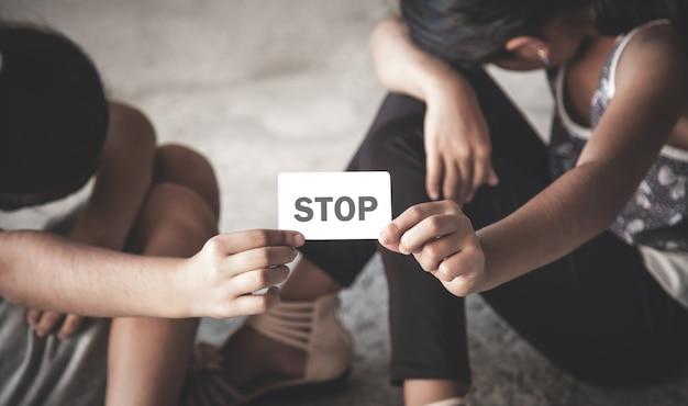 名刺に停止テキストを保持している2人の小さな白人の女の子。