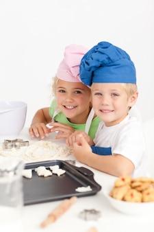 キッチンでクッキーを準備する2人の小さなシェフ