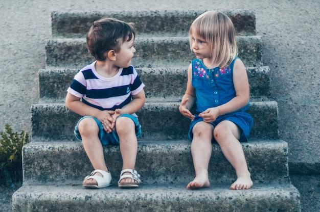 자연 속에서 두 어린 아이, 소녀와 소년, 돌에 앉아, 야외에서 미소로 서로를보고
