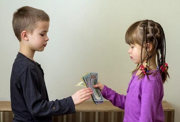 2つの小さな男の子と女の子がドルのお金で遊んで。