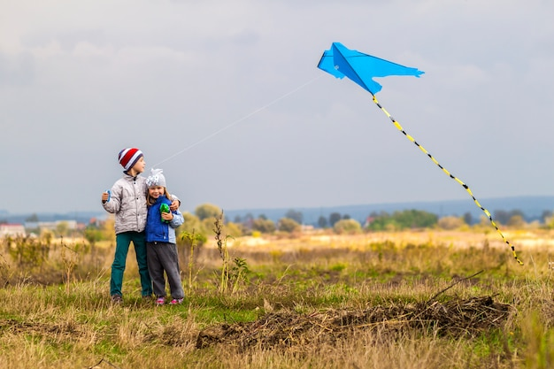 Two little children boy and girl playing outside with a kite