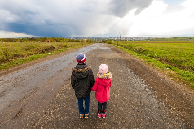 Two little children boy and girl walking on a road