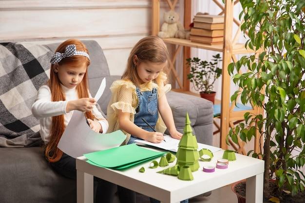 二人の小さな子供たち、家の創造性で一緒に女の子。