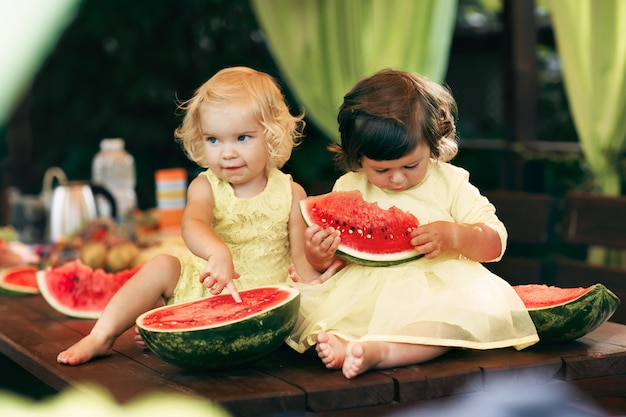 Two little curly girls eating a juicy watermelon in the garden. children eat fruit on the street. healthy food for children. toddler gardening.