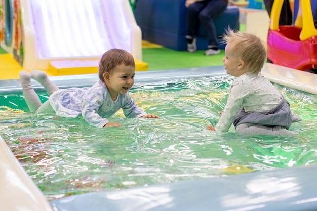 두 명의 작고 귀여운 아기 소녀들이 어린이 놀이터에 있는 장난감 수영장에서 거짓말을 하고 웃고 즐깁니다.