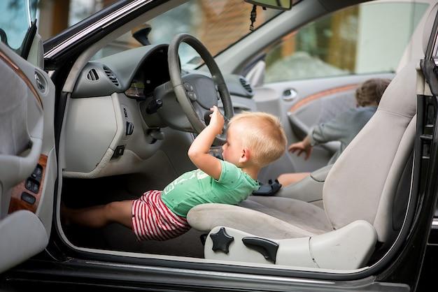 Двое маленьких симпатичных детей - брат и сестра, играющие в машине за рулем.