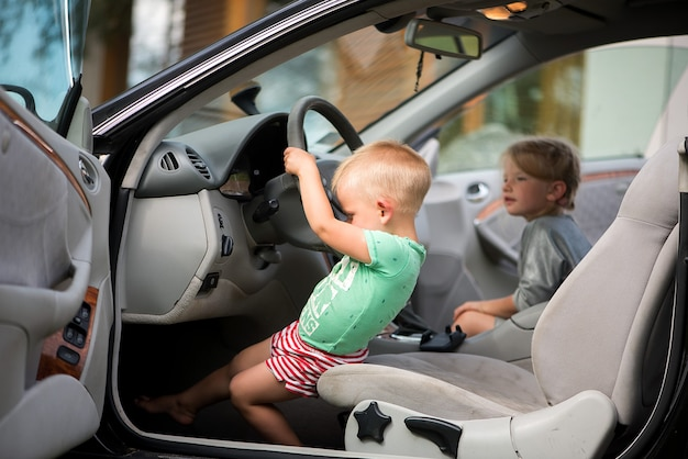Two little cute children - a brother and a sister playing in the car at the wheel.