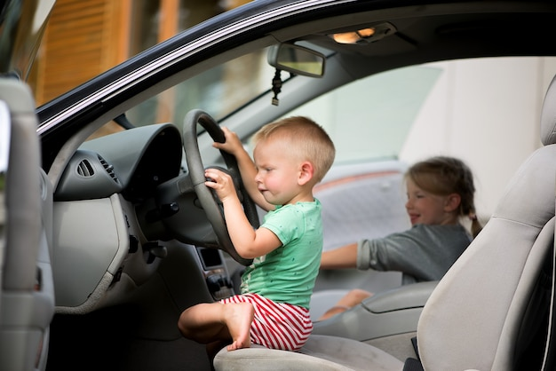Two little cute children - a brother and a sister playing driving in the car at the wheel.