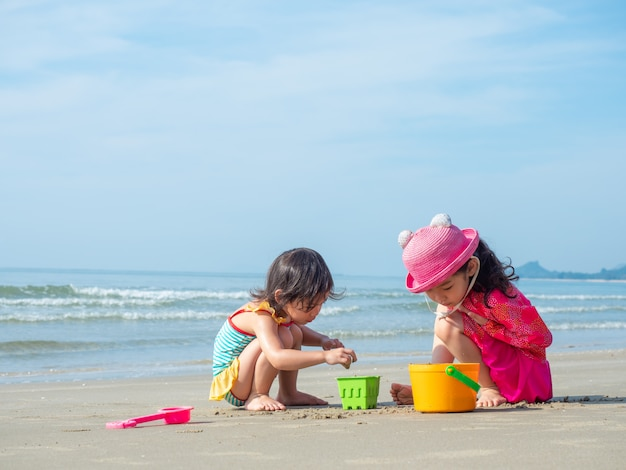 Two little cute girl are playing sand and explore the life on the beach.