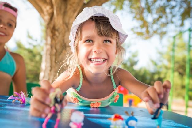 더운 여름 날에 해변에서 휴식을 취하는 동안 야외에서 인형을 연주하는 두 명의 작은 귀여운 소녀. 어린이를위한 활동적인 게임의 개념.