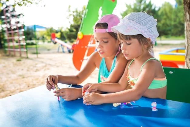暑い夏の日にビーチでリラックスしながら屋外で人形を遊んでいる2人の小さなかわいい女の子