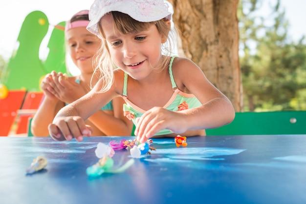 ビーチでリラックスしながら屋外で人形を遊んでいる2人の小さなかわいい女の子