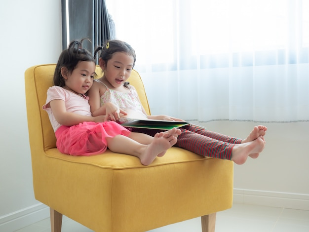 Two little cute girls sitting on yellow chair and reading the book in the room.