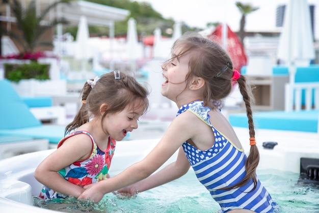 2人のかわいい姉妹がプールで遊んでいます。家族の価値観と友情。