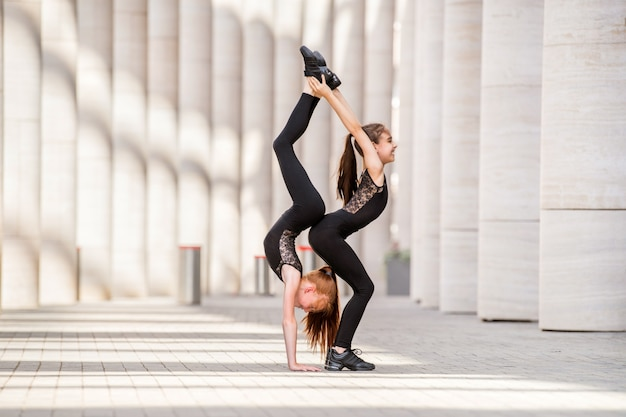 黒のタイトな衣装を着た2人の小さなダンサーのバレリーナが街並みを背景に踊っています。