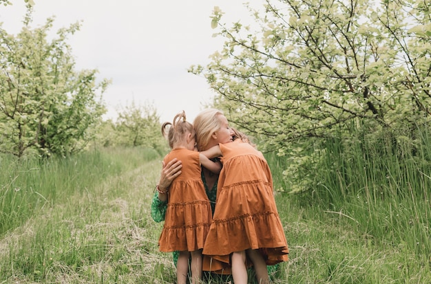 Две маленькие дочери в одинаковых платьях обнимают счастливую маму в яблоневом саду